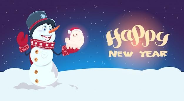 Simbolo sveglio del cane della tenuta del pupazzo di neve della cartolina d'auguri di festa della decorazione del nuovo anno