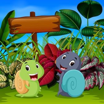 Simpatiche lumache giocano in giardino con la faccia felice