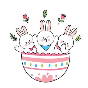 Simpatici conigli di giorno di pasqua del fumetto e grande uovo variopinto.
