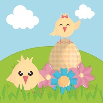 Simpatici pulcini con uovo dipinto nel paesaggio