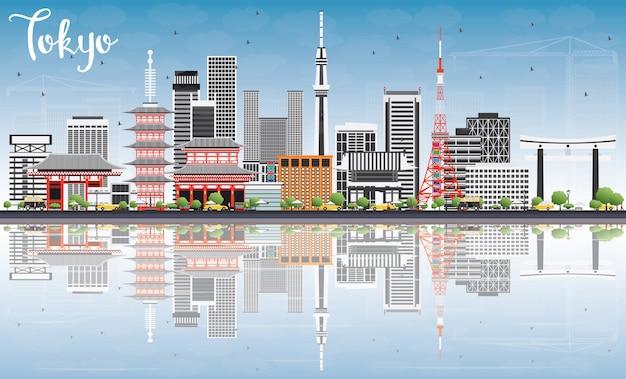 Skyline di tokyo con edifici grigio, cielo blu e riflessioni.