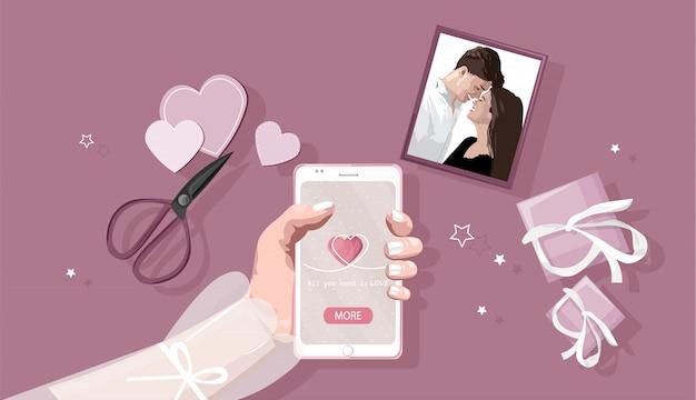 Smart phone della tenuta della giovane donna con la composizione in giorno romantico