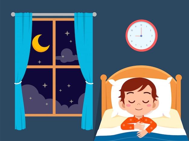 Sonno sveglio felice del ragazzino nella stanza del letto