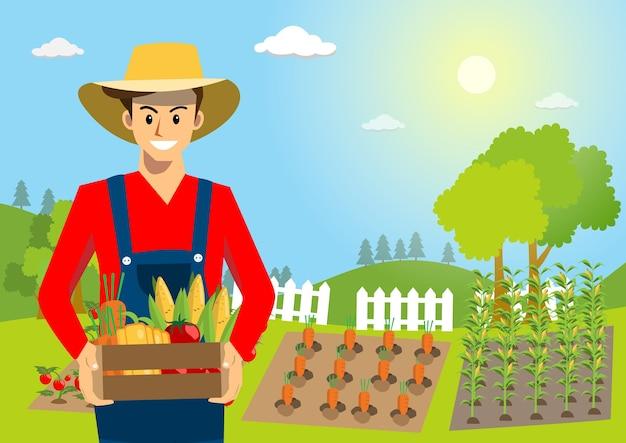 Sorridente giovane agricoltore che tiene la scatola con verdure biologiche.