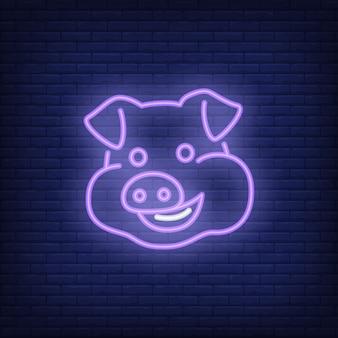 Sorridente personaggio dei cartoni animati di maiale. Elemento di segno al neon. Pubblicità luminosa di notte.
