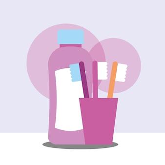 Spazzolini da denti e bottiglia di plastica per lo shampoo