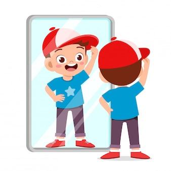 Specchio sveglio felice di uso del ragazzo del bambino nella mattina