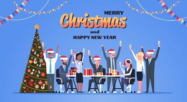 Squadra di affari alzato le mani bicchieri di champagne decorato abete felice anno nuovo celebrazione di buon natale
