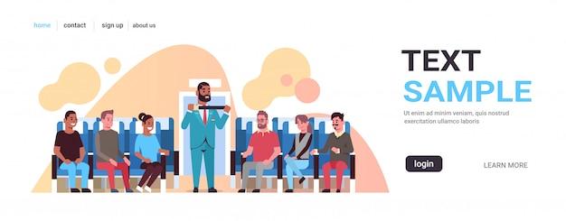 Steward spiegando per i passeggeri della corsa mix come utilizzare la cintura di sicurezza allacciamento di assistente di volo afroamericano in uniforme di sicurezza concetto di dimostrazione aereo bordo interno orizzontale spazio di copia