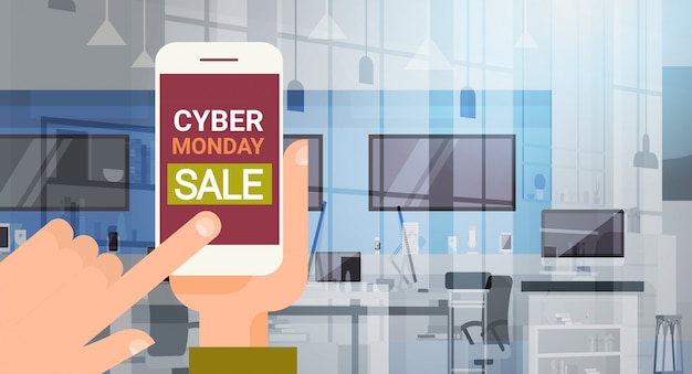 Stretta della mano smartphone con messaggio cyber monday, grande vendita su modern technology store