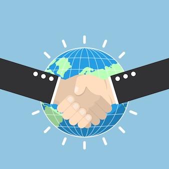 Stretta di mano di affari con il globo della terra