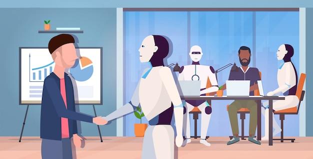Stretta di mano moderna del robot con l'uomo d'affari