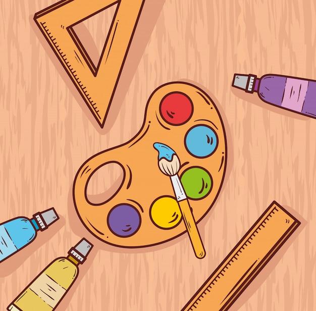 Tavolozza di arte con vernici e pennello sul tavolo di legno