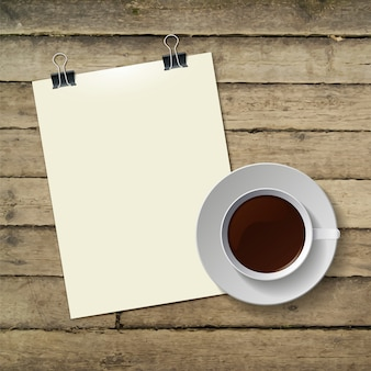 Tazza di caffè caldo e carta per appunti su legno
