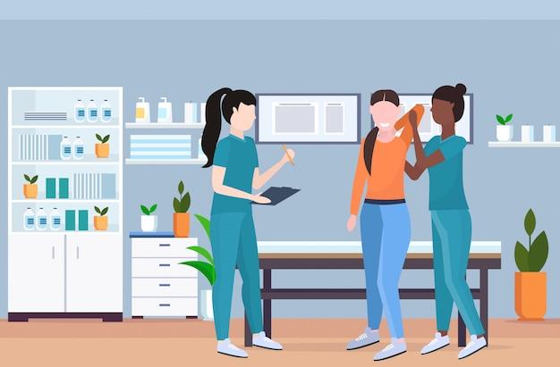 Terapeuta esaminando il paziente infortunato massaggiatrice infermiera facendo guarigione trattamento manuale sport terapia fisica riabilitazione concetto clinica ufficio interno orizzontale integrale