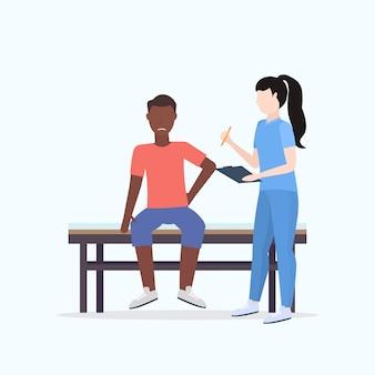 Terapista femminile della lavagna per appunti della tenuta di medico che consulta paziente maschio ferito che si siede sul concetto manuale di terapia fisica di sport del letto integrale