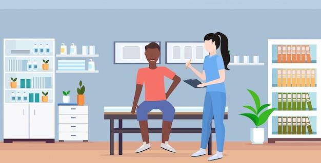 Terapista femminile della lavagna per appunti della tenuta di medico che consulta paziente maschio ferito che si siede sull'orizzontale interno moderno dell'ufficio medico moderno di concetto di terapia fisica di sport manuale del letto