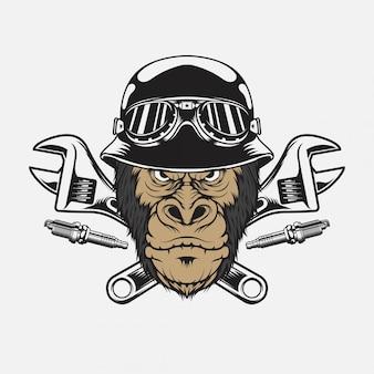 Testa di gorilla vintage indossando casco da motociclista con chiave inglese e candela