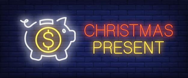 Testo al neon del presente di natale con il porcellino salvadanaio e moneta