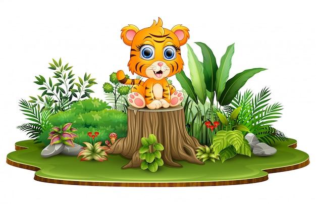 Tigre di bambino felice del fumetto che si siede sul ceppo di albero con le piante verdi