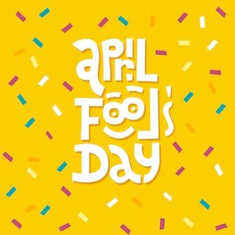 Tipografia dell'iscrizione di april fools day su fondo giallo con i coriandoli