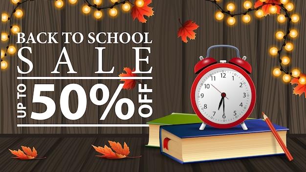 Torna alla vendita della scuola, banner web sconto con struttura in legno, libri di scuola e sveglia