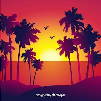 Tramonto sulla spiaggia con sagome di palme