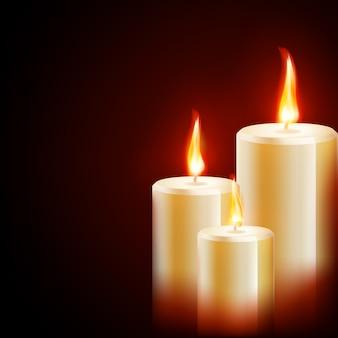 Tre candele su sfondo scuro.