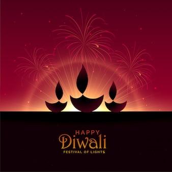 Tre diwali diya con fuochi d'artificio