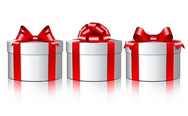 Tre scatole regalo bianche con fiocchi rossi.