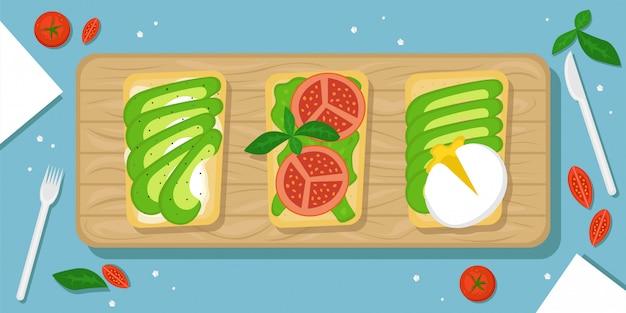 Tre tipi di toast con avocado. bello fondo dell'alimento con il tagliere di legno, i pomodori ciliegia, i cristalli di sale e la coltelleria. illustrazione piatta. la vista dall'alto