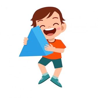 Triangolo sveglio felice di forma della tenuta del ragazzo del bambino