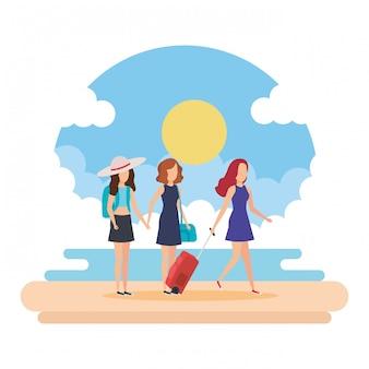 Turisti ragazze con valigie sulla spiaggia