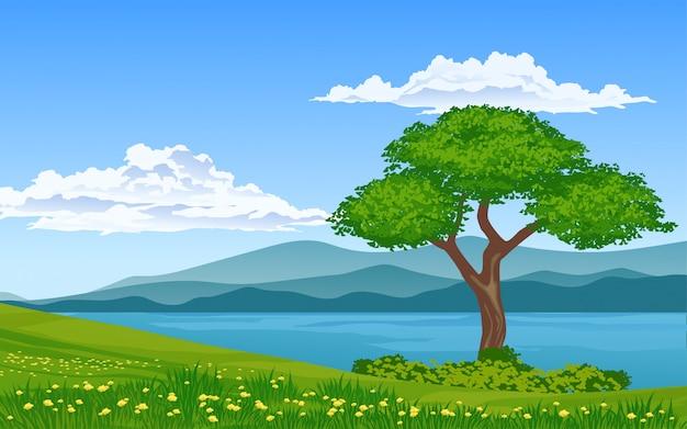 Un albero nel prato con fiume e montagna