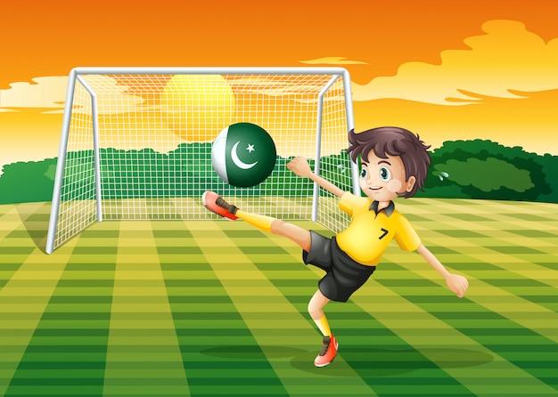 Un atleta calciare la palla con la bandiera del pakistan