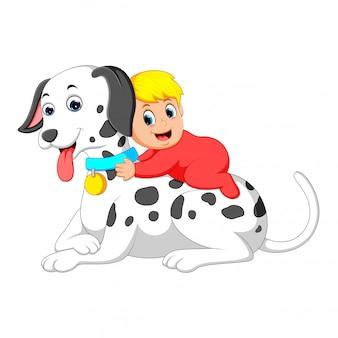 Un bambino carino sta giocando e tenendo in mano il grosso cane bianco