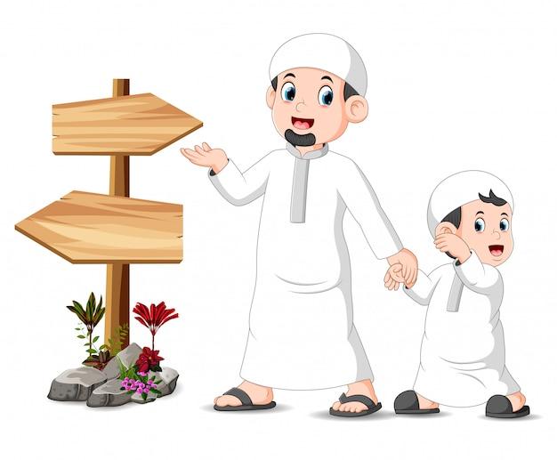 Un bambino con suo padre è in piedi e in posa vicino al cartello di legno bianco