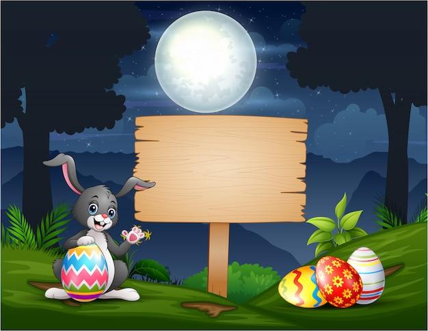 Un coniglietto che tiene l'uovo di pasqua con il segno di legno in bianco alla notte