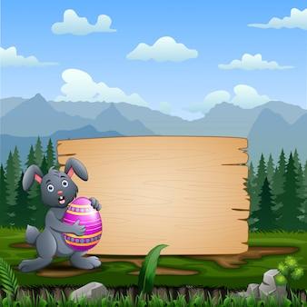 Un coniglietto con uovo di pasqua con cartello in legno bianco