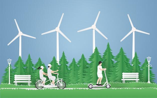 Un giovane ragazzo in sella a uno scooter elettrico, coppia in viaggio in bicicletta nel parco sull'erba verde sullo sfondo del parco.