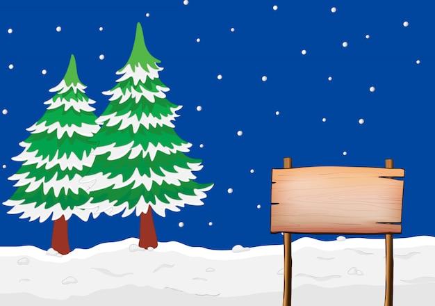 Un'insegna vuota con gli alberi nevosi