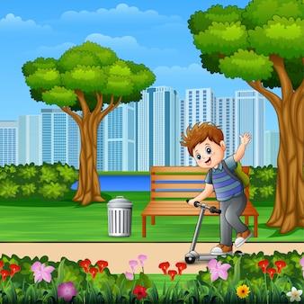 Un ragazzino in sella a uno scooter nel parco della città