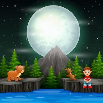 Un ragazzo che pesca con gli animali nella scena notturna