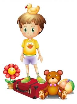 Un ragazzo sopra la scatola rossa con i suoi diversi giocattoli