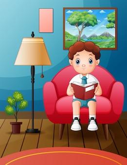 Un ragazzo studente si siede su una sedia morbida mentre legge un libro
