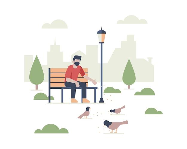Un uomo che indossa una maschera per il viso seduto nel parco pubblico mentre alimenta gli uccelli con l'illustrazione della siluetta del paesaggio della costruzione della città