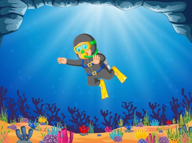Un uomo si sta immergendo sotto lo sfondo blu dell'oceano usando il tubo dell'ossigeno