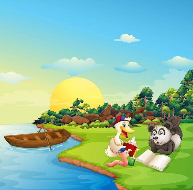 Un verme, un'anatra e un panda che leggono sulla sponda del fiume