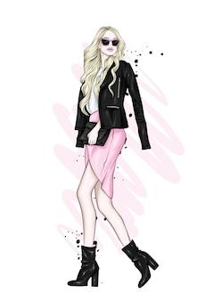 Una bella ragazza con i capelli lunghi in occhiali, una giacca, una gonna e stivali con i tacchi.