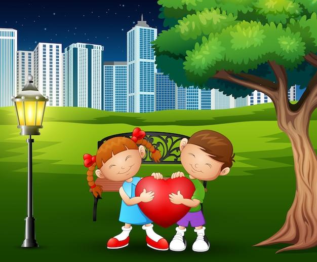Una coppia che tiene a forma di cuore rosso nel parco della città